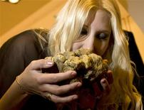 <p>Auction organizer Giselle Oberti smells a 1.08kg white truffle from Marche in downtown Rome November 25, 2008. The truffle will be sold during a satellite-linked charity auction in Macau. REUTERS/Tony Gentile</p>