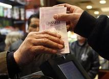 <p>A cashier hands a customer a Mega Millions lottery ticket in New York, March 6, 2007. REUTERS/Eric Thayer</p>