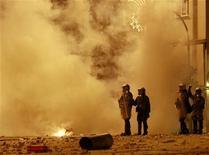 <p>Полиция наблюдает за беспорядками у здания Афинского университета 8 декабря 2008 года. Новая волна беспорядков может прокатиться по Греции во вторник, когда состоятся похороны подростка, убитого греческими полицейскими, и в среду, когда запланирована всеобщая забастовка. REUTERS/John Kolesidis</p>