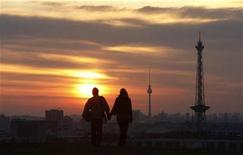 <p>People walk as the rising sun illuminates Berlin's skyline September 1, 2008. REUTERS/Fabrizio Bensch</p>