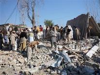 <p>Жители на месте взрыва в городе Бунер 28 декабря 2008 года. Жертвами взрыва, прогремевшего возле избирательного участка в северном Пакистане, стали как минимум 22 человека, в том числе 4 ребенка, сообщили местные правоохранительные органы. REUTERS/Abdul Rehman</p>