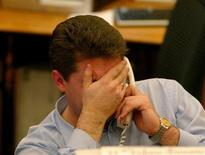 <p>A man covers his face at his desk in this 2004 file photo. REUTERS/Sergei Karpukhin</p>