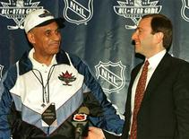 <p>Willie O'Ree, (L) the first African-American to play in the NHL is congratulated by Commissioner Gary Bettman at a news conference in Vancouver January 17, 1998. REUTERS/Peter Jones</p>