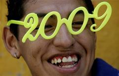 <p>A street vendor smiles as he sells products for the new year in a market in Lima, December 29, 2008. REUTERS/Mariana Bazo</p>