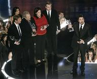 """<p>Cast and crew members of """"The Dark Knight,"""" actor Aaron Eckhart (L), director Christopher Nolan (C) and actor Christian Bale (R) react after winning four awards at the 35th annual People's Choice awards in Los Angeles January 7, 2009. REUTERS/Danny Moloshok</p>"""