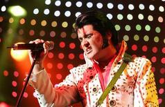 <p>Singer Grahame Patrick performs dressed as Elvis Presley during a show in Berlin, August 15, 2007. REUTERS/Hannibal Hanschke</p>