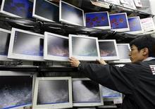 <p>Foto de archivo de un empleado de una tienda limpiando monitores de cristal líquido en Tokio, 8 feb 2007. La venta de computadoras personales en Asia cayó un 5 por ciento interanual en el cuarto trimestre, en la primera baja de la región en una década, debido a que la crisis mundial afectó a la demanda, reveló el lunes un informe de INTERNATIONAL DATA CORP (IDC). REUTERS/Issei Kato</p>