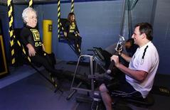 <p>A gym member does some exercises for photographers using human weights at a Gymbox gym in London January 21, 2009. REUTERS/Stephen Hird</p>