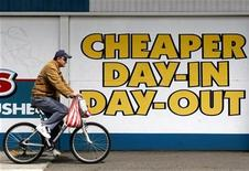 <p>A cyclist rides past an advertisement outside a supermarket in surburban Melbourne October 14, 2008. REUTERS/Mick Tsikas</p>