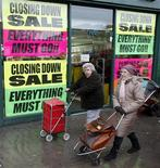 <p>Two women push their shopping trolleys past a shop advertising a closing down sale in London January 22, 2009. REUTERS/Stephen Hird</p>