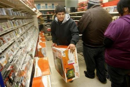 Christofer Aboype carries an LCD TV set at the K-Mart store in Burbank, California November 28, 2008. REUTERS/Fred Prouser