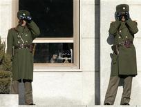 <p>Солдаты армии КНДР смотрят в бинокль на северную часть деревни Панмунждом, в которой был подписан договор о прекращении огня в 1953 году и расположенной в демилитаризованной зоне, разделяющей КНДР и Южную Корею 6 декабря 2008 года. Рост напряженности в отношениях между КНДР и Южной Кореей поставил Корейский полуостров на грань войны, сообщил в воскресенье официальный Пхеньян. REUTERS/Lee Jae-Won</p>