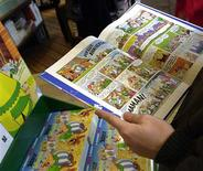 """<p>A man reads a copy of """"Asterix and Latraviata,"""" the 31st in the Asterix series, in a file photo. REUTERS/File</p>"""