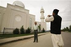 <p>Mohammed Mangla takes his brother Saleh's photograph outside the Baitun Nur mosque, the largest mosque in Canada, in Calgary July 4, 2008. REUTERS/Todd Korol</p>