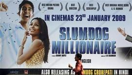 "<p>A man walks past a billboard displaying a poster of the film ""Slumdog Millionaire"" in Mumbai January 20, 2009. REUTERS/Punit Paranjpe</p>"