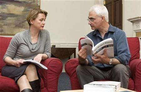 Chancellor Alistair Darling (R) holds a copy of his Pre-Budget Report during a meeting with Chief Secretary to the Treasury Yvette Cooper in his office at the Treasury in London, November 23, 2008. REUTERS/Carl Court/Pool