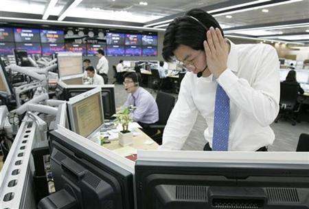 A foreign currency dealer of the Korea Exchange Bank talks on phone as he looks at monitors showing exchange rates at the bank's headquarters in Seoul February 3, 2009. REUTERS/Jo Yong-Hak