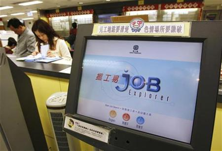 Job seekers go through vacancies beside a monitor at a Labour Department job centre in Hong Kong February 17, 2009. REUTERS/Bobby Yip