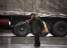 <p>A migrant worker walks past a truck with his belongings over his shoulder as he walks through the town of Xichuan, Henan province February 18, 2009. REUTERS/David Gray</p>