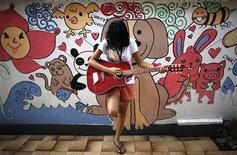 <p>A girl practises the guitar during a free guitar workshop for street children, conducted by instructor Ramon Ramos (not pictured), at a shelter in Manila February 19, 2009. REUTERS/John Javellana</p>
