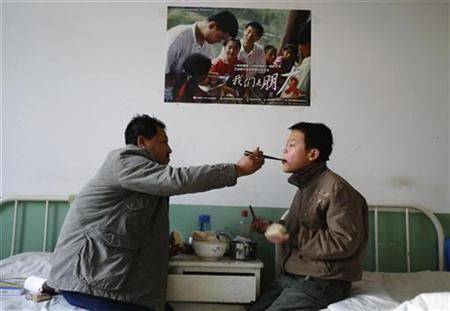 An HIV-infected man feeds his step son, who is also HIV-infected, at a red ribbon primary school known as the Green Harbour in Linfen, Shanxi province November 29, 2008. The school, operated by a hospital since 2004, provides cultural courses and lodging for 13 HIV-infected children aged 8 to 13. By September 2008, China reported about 260,000 HIV positive in total, among whom 77,000 had developed AIDS and 34,000 have died. REUTERS/Stringer