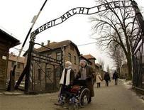 """<p>Foto de archivo de supervivientes del campo de concentración nazi de Auschwitz cruzan un portón metálico con el emblema """"Arbeit macht frei"""" (el trabajo los hará libres) en Oswiecim, Polonia, 27 ene 2009. Polonia ha pedido donaciones internacionales para preservar las instalaciones y exhibiciones en el antiguo campo de concentración nazi de Auschwitz, donde más de un millón de judíos murieron durante la Segunda Guerra Mundial. REUTERS/Peter Andrews</p>"""