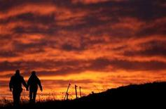 <p>A couple hikes during sunset on the car free island of Hiddensee in the Baltic Sea near village Kloster December 31, 2007. REUTERS/Hannibal Hanschke</p>