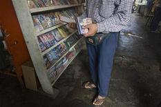 <p>A customer looks at pirated CDs and DVDs on display at a marketplace in Asuncion, a day before the country holds presidential elections, April 19, 2008. REUTERS/Enrique Marcarian</p>
