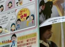 <p>A person walks past an anti-scam poster in Taipei February 25, 2009. REUTERS/Pichi Chuang</p>