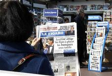 <p>A woman reads the French daily newspaper Le Figaro next to a newsstand in Nice, southeastern France, February 24, 2009. REUTERS/Eric Gaillard</p>