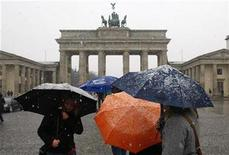 <p>Tourists protect themselves with umbrellas as they gather in front the Brandenburg Gate as first snow falls in Berlin in this file photo from November 21, 2008. REUTERS/Fabrizio Bensch</p>