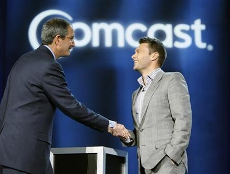 Comcast CEO Brian Roberts (L) shakes hands with American Idol host Ryan Seacrest during Robert's keynote address at the Consumer Electronics Show in Las Vegas, Nevada in this file photo from January 8, 2008. REUTERS/Rick Wilking