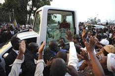 <p>Pope Benedict XVI waves at the crowd from his Popemobile at the end of the mass of Vespers at Marie Reine des Aprotes Basilic in Yaounde March 18, 2009. REUTERS/Alessandro Bianchi</p>
