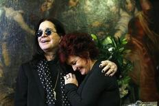 <p>Ozzy and Sharon Osbourne smile as they pose in front of some of their belongings to be auctioned in Beverly Hills, California November 26, 2007. REUTERS/Mario Anzuoni</p>