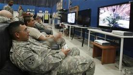 <p>U.S. soldiers play computer games on a television set at the recreational hall of a U.S. military Camp Marez in Mosul, 390 km (240 miles) north of Baghdad January 30, 2009. REUTERS/Erik de Castro</p>