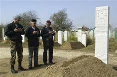 <p>Трое мужчин молятся на могиле Руслана Ямадаева в Гудермесе 26 сентября 2008 года. Герой России и оппонент президента Чечни Рамзана Кадырова Сулим Ямадаев был убит в ОАЭ в минувшие выходные. REUTERS/Said Tsarnayev</p>