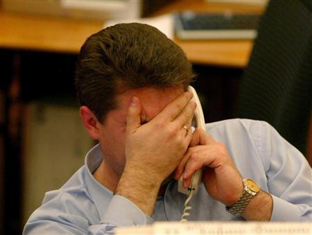 A trader covers his face as he speaks on the phone during in Moscow, June 18, 2004. REUTERS/Sergei Karpukhin