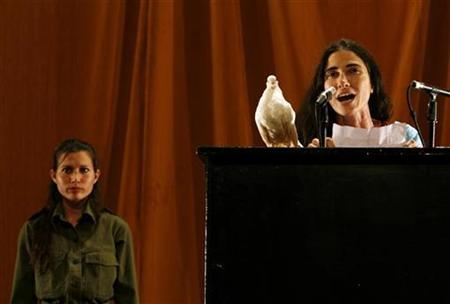 Cuban blogger Yoani Sanchez takes the stage during a performance at the 10th Biennale of Contemporary Art in Havana March 29, 2009. REUTERS/Enrique De La Osa