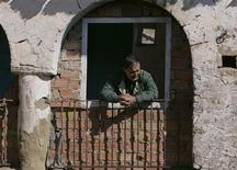 <p>A man looks from the window of his house in Dellys February 26, 2009. REUTERS/Louafi Larbi</p>