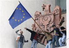 <p>Демонстранты размахивают флагом Евросоюза, забравшись на козырек здания парламента в Кишиневе 7 апреля 2009 года. Протесты в Кишиневе, порожденные недовольством оппозиции парламентскими выборами, оставившими у власти коммунистов, препятствуют сохранению стабильности у самых границ Евросоюза. Однако блок старается дистанцироваться от спора, дабы не осложнить и без того непростые отношения с Москвой. REUTERS/Gleb Garanich</p>