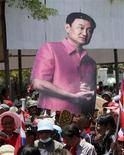 <p>Supporters of ousted Thai prime minister Thaksin Shinawatra carry his image while leaving the Government House area in Bangkok April 14, 2009. REUTERS/Chaiwat Subprasom</p>