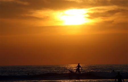 A surfer rides on the waves during sunset at Tamarindo beach, in Santa Cruz de Guanacaste, 250 miles (402 km) north of San Jose, Costa Rica, April 28, 2008. (REUTERS/Juan Carlos Ulate)