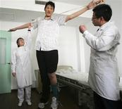 <p>Zhao Liang, who may be the world's tallest person, has his arms measured by doctors before foot surgery at a hospital in Tianjin municipality April 13, 2009. At 2.46 metres (8 ft 1 in) tall, Zhao may well be the world's tallest person. All he needs is to be officially measured. The 27-year-old was recently measured by doctors who were treating him for a foot injury, and was found to be some 10 cm higher than Bao Xishun, the 57-year-old Chinese man currently holding the Guinness World Record for tallest man. Picture taken April 13, 2009. REUTERS/China Daily</p>