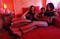 """<p>Румынские проститутки позируют на своем рабоче месте в публичном доме """"Pussy Club"""" в Берлине 15 апреля 2009 года. Мировому финансовому кризису потребовалось не так много времени, чтобы его щупальца дотянулись и до немецких представительниц древнейшей профессии. REUTERS/Hannibal Hanschke</p>"""