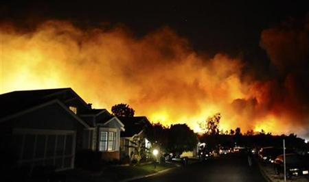 Fire lights up the night over houses on the second day of a wildfire in Sylmar, California October 13, 2008. REUTERS/Gene Blevins
