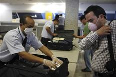 <p>Security guards wear masks as they inspect luggage from passengers heading to Mexico City at Mariano Escobedo international airport in Monterrey, northern Mexico April 26, 2009. Governments around the world rushed on Sunday to check the spread of a new type of swine flu that has killed up to 81 people in Mexico and infected around a dozen in the United States. REUTERS/Tomas Bravo</p>