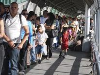 <p>U.S. residents and tourists wait in line to cross to El Paso, Texas at the international border crossing bridge of Paso del Norte in Ciudad Juarez, April 25, 2009. REUTERS/Alejandro Bringas</p>