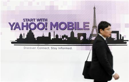 A visitor walks past a Yahoo advertisement at the GSMA Mobile World Congress in Barcelona, February 18, 2009. REUTERS/Albert Gea