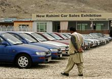 <p>An Afghan man walks in front of a car seller in Kabul May 3, 2009. Over seven years after the fall of the Taliban the streets of Kabul are heaving with cars, but far from hopeful signs of development, many are dangerous scrap that clog the capital's skies with pollution, experts say. REUTERS/Omar Sobhani</p>