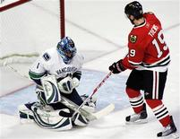 <p>Vancouver Canucks goalie Roberto Luongo (L) covers up the puck as Chicago Blackhawks' Jonathan Toews waits for a rebound in the first period during Game 4 of their NHL Western conference semi-final hockey game in Chicago May 7, 2009. REUTERS/Frank Polich</p>